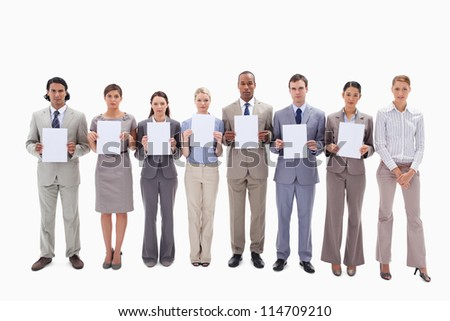 Business people holding seven white supports for letters against white background - stock photo