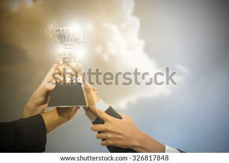 Business people holding trophy award after win competitor. - stock photo