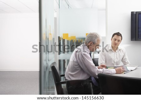 Business people in conference room reviewing documents - stock photo