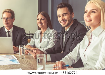 Business people in formal wear are participating in the conference, handsome man in the middle is looking at camera and smiling