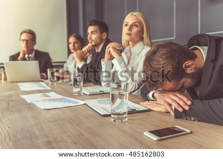 people bored at work. business people in formal wear are participating the conference, man foreground is bored at work