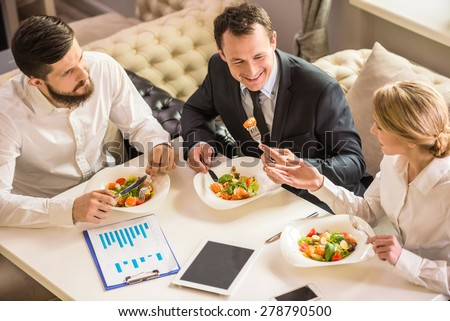 Business people in formalwear discussing something during business lunch. - stock photo