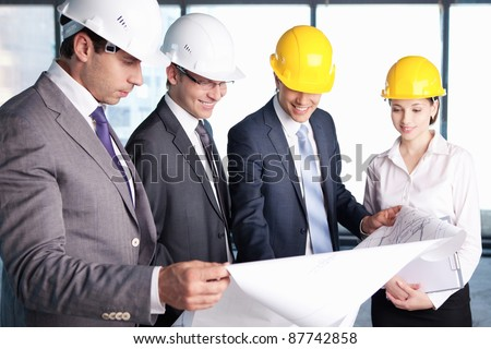 Business people in hard hats at construction site - stock photo