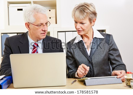 Business people in office comparing tablet computer and laptop - stock photo