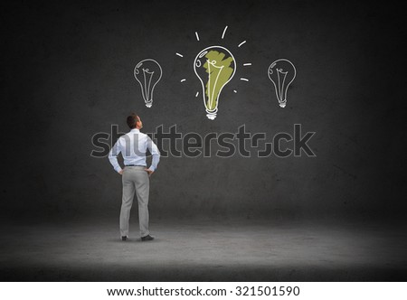 business, people, inspiration and idea concept - businessman at lighting bulb doodles over concrete room background from back - stock photo