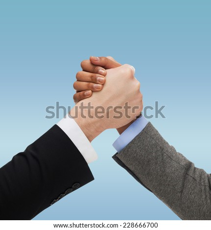 business, people, international and competition concept - close up of two hands multiracial armwrestling or handshake over blue background - stock photo