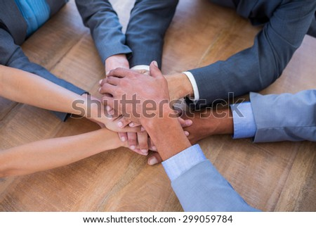 Business people joining hands in a circle in the office - stock photo
