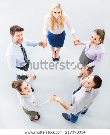Business people joining hands in circle - stock photo