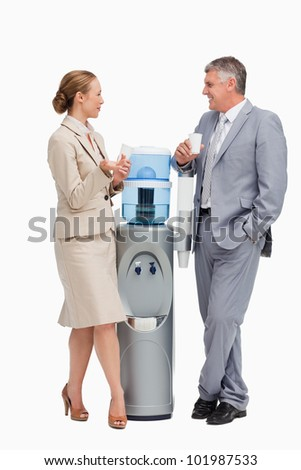 Business people laughing next to the water dispenser against white background