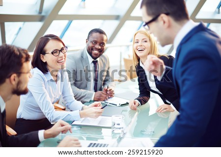 Business people laughing together at meeting - stock photo