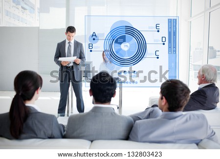 Business people listening and looking at blue diagram interface in a meeting