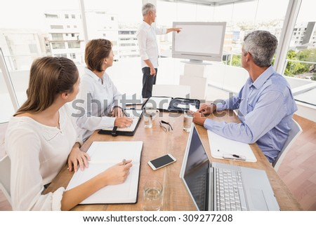 Business people listening to colleagues presentation in the office - stock photo