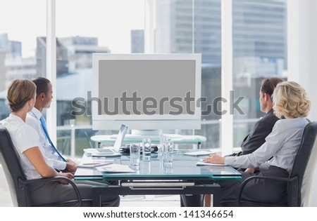 Business people looking at a screen during a video conference - stock photo