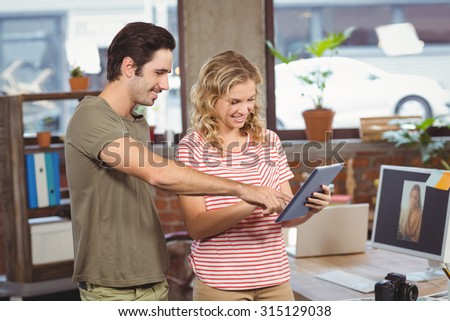 Business people looking at digital tablet while standing in office - stock photo
