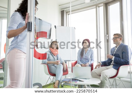 Business people looking at female colleague standing in sliding door - stock photo