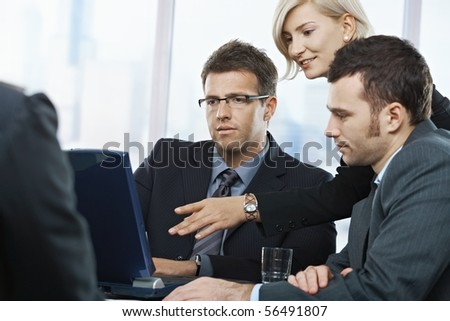 Business people looking at laptop, talking at meeting table in office, - stock photo