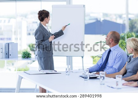 Business people looking at meeting board during conference in office - stock photo