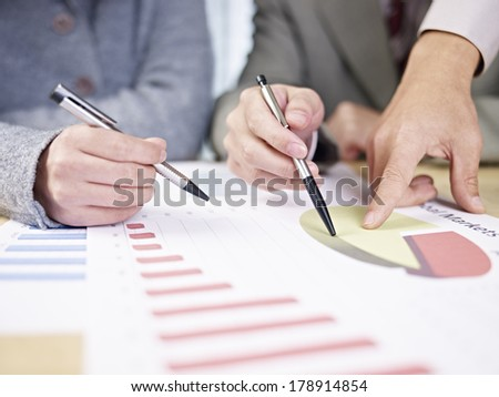 business people looking at report and having a discussion in office. - stock photo
