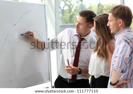 Business people looking at their leader while she explaining something on whiteboard - stock photo