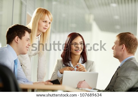 Business people looking at their male colleague as he has come up with a really good idea - stock photo