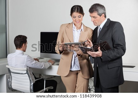 Business people making appointments with tablet pc and datebook - stock photo