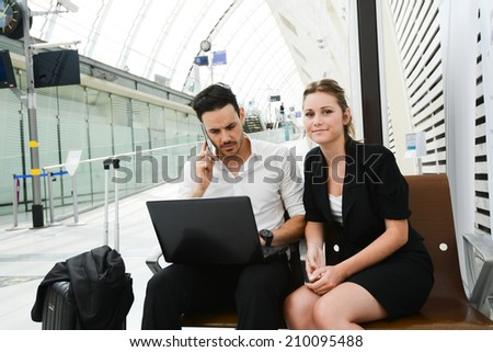 business people man and woman sitting in public station and working with computer in public wifi area - stock photo