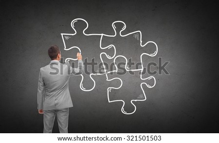 business, people, management and strategy concept - businessman drawing puzzle from back over dark gray concrete wall background