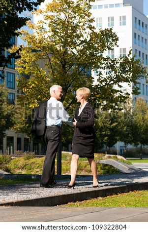 Business people - mature or senior - pass by and greet