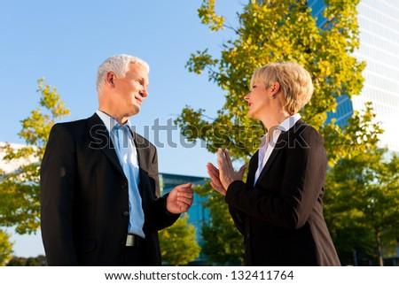 Business people - mature or senior - standing in a park outdoors talking - stock photo