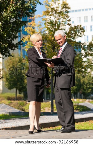 Business people - mature or senior - talking outdoors and discussing a document