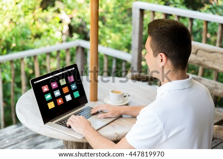 business, people, media and technology concept - close up of businessman with computer menu icons on laptop screen working outdoors on summer terrace and drinking coffee - stock photo