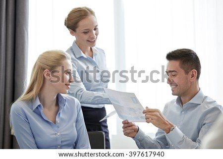 business, people, meeting and teamwork concept - smiling businesswoman giving papers to man in office - stock photo