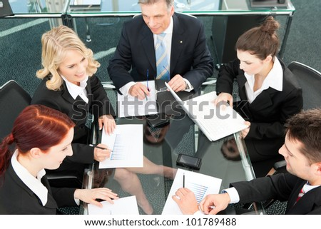 Business people - meeting in an office, the businesspeople are discussing a document - stock photo