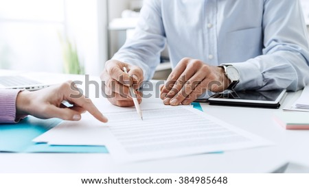 Business people negotiating a contract, they are pointing on a document and discussing together - stock photo
