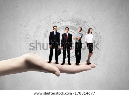 Business people of different professions standing on palm