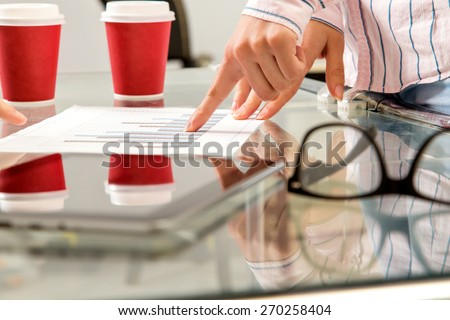 Business people on a meeting, analyzing finance charts - stock photo