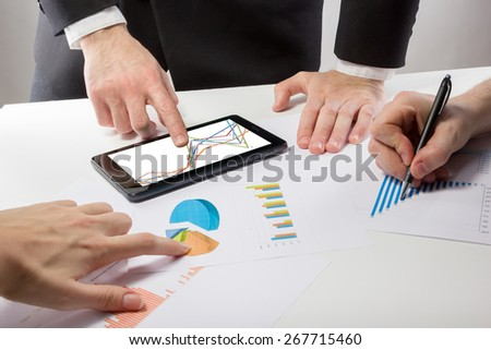 Business people on a meeting analyzing financial reports discussing the charts and graphs showing the results of their successful teamwork