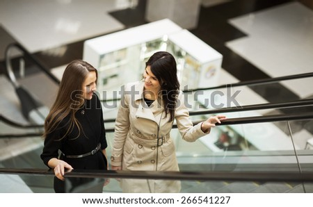 business people on escalator, two young businesswomen talking