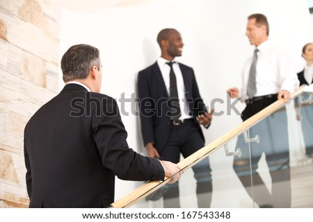 Business people on staircase. Mature man in formalwear moving up by staircase while his colleagues moving down - stock photo