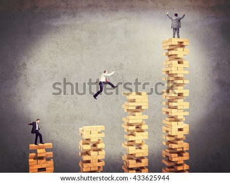 business people on wood toy tower block - stock photo