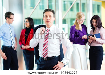 Business people or team in office, a man is looking to the viewer