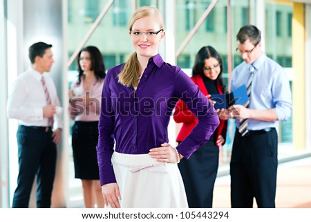 Business people or team in office, a woman is looking to the viewer