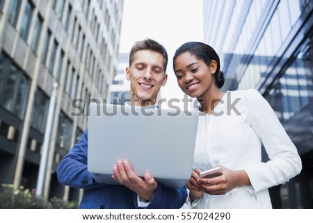 Business people outdoors during the break. Two young  business people using laptop together while standing outside office building