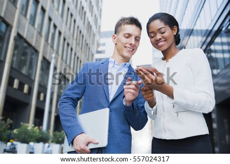 Business people outdoors. Handsome business man and his beautiful female colleague using phone together while crossing the street, office buildings on background