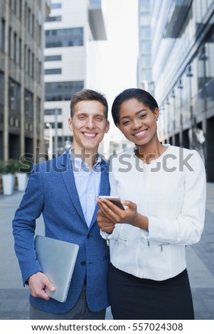 Business people outdoors with gadgets. Handsome business man and his beautiful female colleague looking to camera while standing outside the office, urban scene background