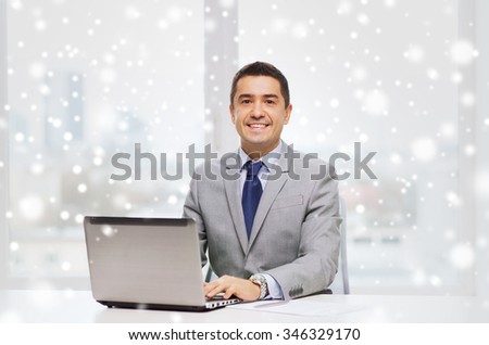 business, people, paperwork and technology concept - smiling businessman with laptop computer and papers working in office over snow effect
