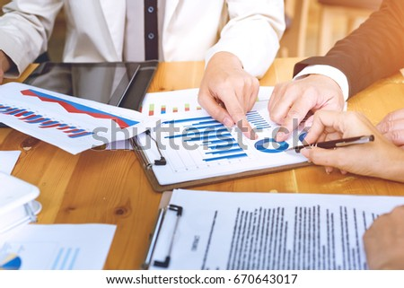 Business people point finger analyzing at the documents income charts and graphs good teamwork on office table. Teamwork successful Meeting Workplace strategy with graph financial diagram.