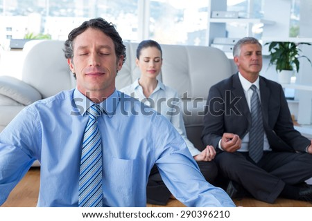 Business people practicing yoga in living room - stock photo