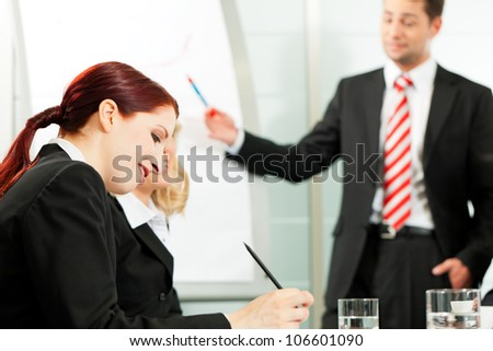 Business people - presentation within a team, a colleague is standing on the flipchart - stock photo