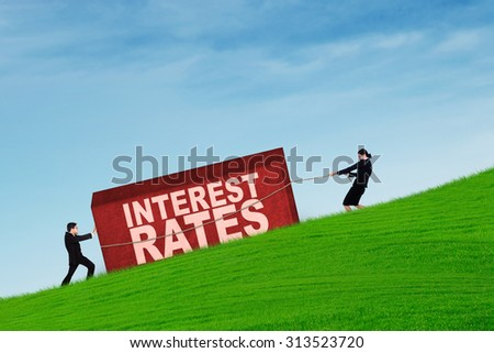Business people pulling a box with interest rates word on up hill - stock photo